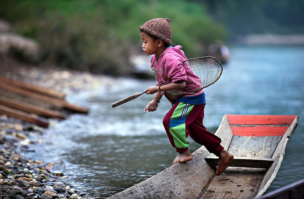 Tennis anyone? A boy playing on the Nam Ou (river), Laos.