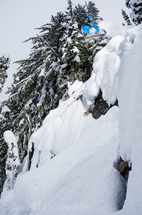 Profesional snowboarder Shin Campos launches off a snowy cliff on Whistler Mountain.
