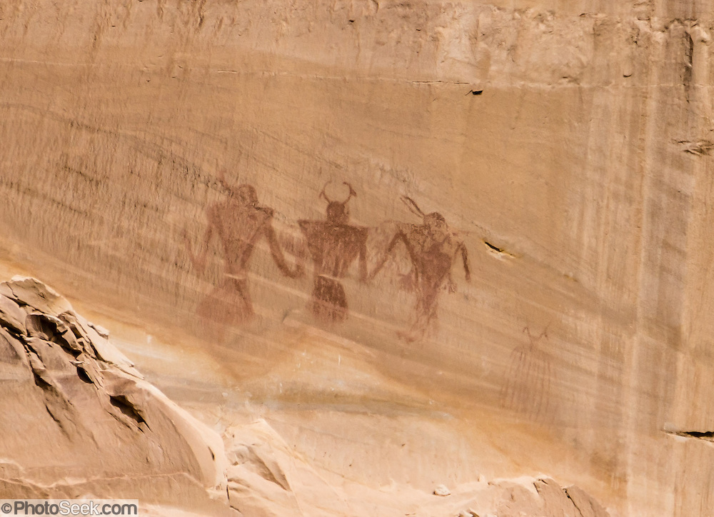 Pictographs: across the canyon from Lower Calf Creek Falls trail, see three large figures painted with red pigment at the bottom of a smooth wall streaked with desert varnish. (Pictographs are painted images while petroglyphs are carved or pecked into the rock surface.) Typical of Fremont style rock art, these images have trapezoidal shape, depictions of arms and legs, and elaborate head dresses. Their meaning is unknown and subject to speculation. Hike Lower Calf Creek Falls trail 6 miles round trip (600 feet gain), in Grand Staircase Escalante National Monument, Utah, USA. Directions: From the town of Escalante, drive 15 miles east on Scenic Byway 12 to Calf Creek Recreation Area day-use parking and campground.