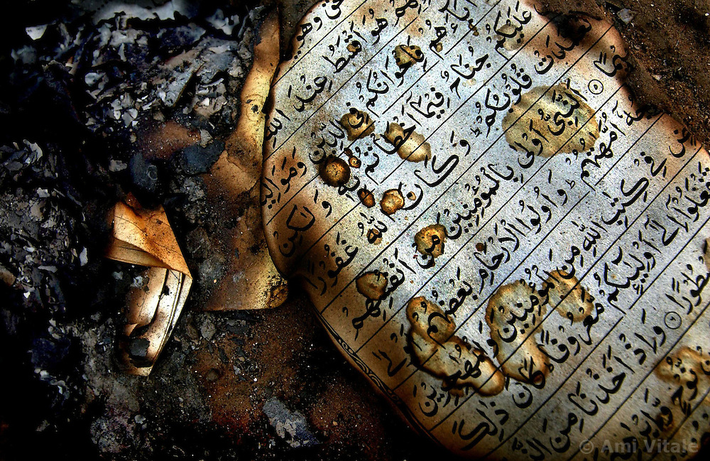A burned Koran sits outside of the home of a murdered Muslim politician in Ahmedabad, India. Troops arrived in India's riot-torn western state of Gujarat but were unable to quell the worst communal bloodshed in a decade.