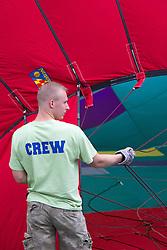 crew member of a hot air balloon team working on a balloon