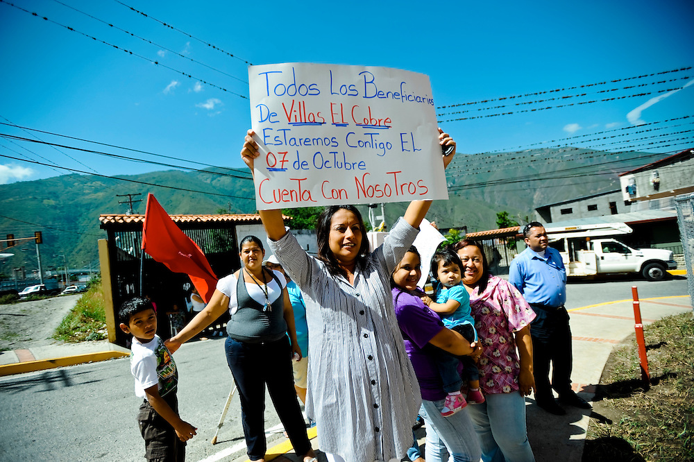 "A pregnant woman at the El Cobre housing development in Ejido, Venezuela is filmed by a camera crew from the state tv channel as she holds a sign that says, ""All the beneficiaries of the El Cobre Villas will be with you the 7th of October, count on us"".  After filming, the government tv producer said she should instead make a sign that says, 'I'm a Chavista and so is my unborn baby', because he claimed, it made for better television."