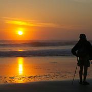 A photographer photographs the sun setting over the Pacific Ocean from a beach in Santa Cruz, California.