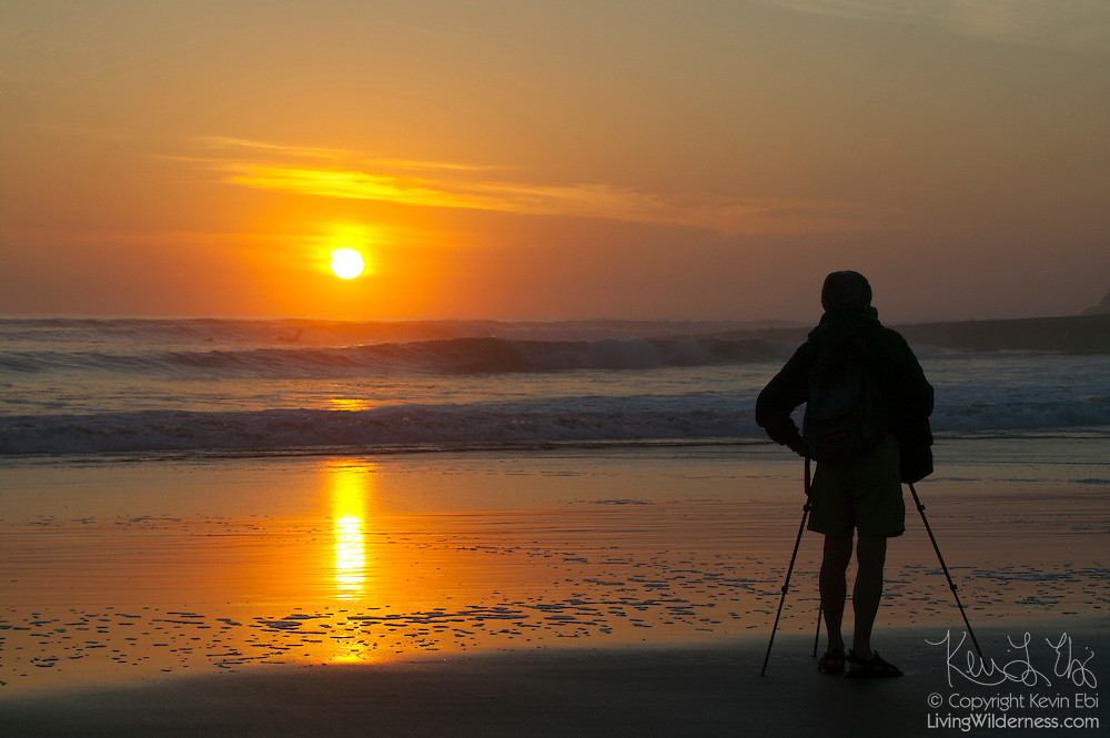 A photographer photographs the sun setting over the Pacific Ocean from a beach in Santa Cruz, California.