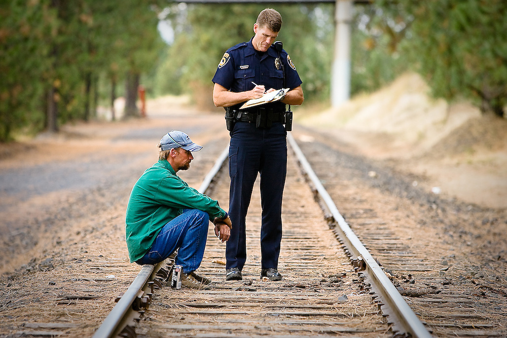 JEROME A. POLLOS/Press ..Coeur d'Alene Police officer John Kelly questions Jeff Pringle following a fire at a transient camp Sept. 25 near Northwest Blvd. Pringle was later arrested for arson.