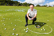 140604 ISON Golf Ball Drop<br /> Captain Mike Burns of Atlas Helicopters with two balls which landed in the hole after he dropped 1,000 golf balls from a Squirrel helicopter flying at 90 feet above Cowdray Park Golf Club in Midhurst, West Sussex for charity. The balls had been sold for &pound;5 each with the owner of the ball closest to the hole winning &pound;500. The rest of the money raised was donated to Treloar School and College in Alton, Hampshire, which provides education, care, therapy, medical support and independence training to young people with physical disabilities. Two balls landed in the hole. <br /> Picture date Wednesday 4th June, 2014.<br /> Picture by Christopher Ison. Contact +447544 044177 chris@christopherison.com