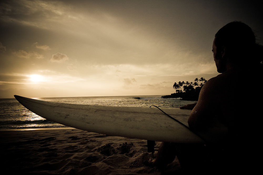 A surfer, Lyle Carlson, sits on the beach after a surf session at Waimea Bay, North Shore, Oahu, Hawaii.
