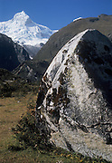Peru, Andes Montain Range - Cordillera de los Ades, Cordillera Blanca mountain range, snow-covered Mount Huandoy (6395 m), with boulder in foreground.