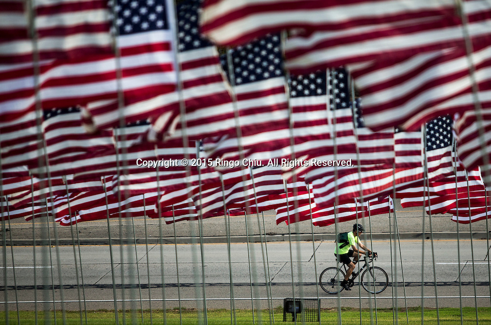 A cyclist rides past the 3,000 US flags are displayed at Pepperdine University to mark the 14th anniversary of the 9/11 terror attack, September 10, 2015 in Malibu, California.  Photo by Ringo Chiu/PHOTOFORMULA.com)