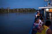 Passengers relax on the 'entertainment deck' aboard the Avenger III.The Avenger III is a passenger ship making the twice a month journey from the frontier town of Tabatinga in the Tr&ecirc;s Fronteiras region of Northwestern Brazil, to the capital of the State of Amazonas, Manaus. It&rsquo;s also where the Rio Amazonas enters Brazil from its source in neighboring Peru. <br /> <br /> Carrying passengers and crew totaling almost 200 and small cargo, the ship meanders its way along the Rio Amazonas and Rio Solimoes for four days and three nights. Stopping at half a dozen or so makeshift ports en-route, the service provides a vial link for communities along the river to get products to the city and more importantly, in the absence of roads or airfields, provide a means for the sick to reach care in the city of Manaus.<br /> <br /> For those not fortunate to be accommodated in one of the two or three cabins available, home is space found for a self supplied hammock amongst the kaleidoscopic web of coloured fabrics. <br /> <br /> By the second day, negotiating a stroll from port to starboard can seem more like negotiating an assault course of tangled ropes and personal baggage deliberately piled high to protect ones personal space.<br /> <br /> Food served three times daily is adequate, a staple of soups, chicken, rice and noodles. An &lsquo;entertainment&rsquo; deck on the top floor provides ample opportunity to be social engaging in card and board games with beer swilling, chain smoking locals.