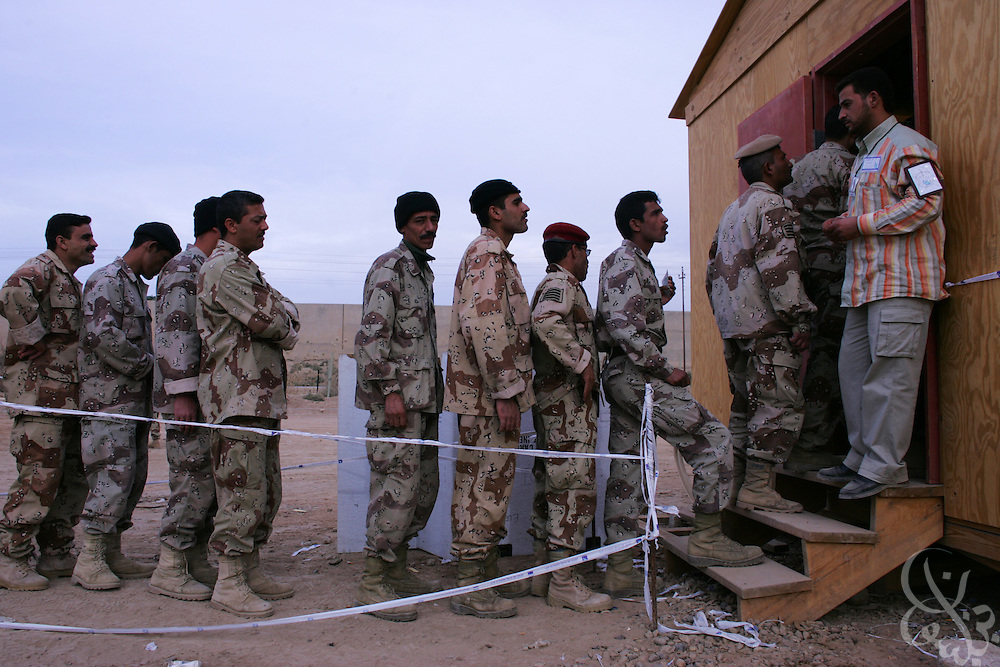 Iraqi Army soldiers wait to cast their ballots for Iraq's national election at Camp Ramadi military base in Ramadi, Iraq on Monday, Dec. 12, 2005. Iraqi security forces voted three days ahead of the National election because they will be busy on election day securing balloting locations for the general public.