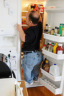 Chris Kotzian climbs into his refrigerator to reach items at the top in his kitchen in Thornton, Colorado March 25, 2010.  At about four-feet-tall,  Chris is a achondroplasia dwarf with a rare genetic disorder of bone growth.  Preferring to be called a little person he is active in the Little People of America, the only dwarfism support organization that includes all 200+ forms of dwarfism.  REUTERS/Rick Wilking (UNITED STATES)