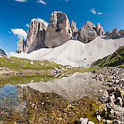 """A pond reflects Tre Cime di Lavaredo (Italian for """"Three Peaks of Lavaredo,"""" also called Drei Zinnen or """"Three Merlons"""" in German), which are distinctive icons of the Alps, in the Sexten Dolomites of northeastern Italy, Europe. Until 1919 the peaks formed part of the border between Italy and Austria. Now they lie on the border between the Italian provinces of South Tyrol and Belluno and still are a part of the linguistic boundary between German-speaking and Italian-speaking majorities. Cima Grande rises to 2999 meters (9839 feet), between Cima Piccola  2857 m (9373 ft) and Cima Ovest  or """"Western Peak"""" 2973 m (9754 ft). The Dolomites were declared a natural World Heritage Site (2009) by UNESCO. Panorama stitched from 9 overlapping photos."""