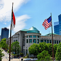 Museum of Natural Sciences and Downtown Skyline at Raleigh, North Carolina<br /> Raleigh, North Carolina is named after Sir Walter Raleigh, the English aristocrat, spy, explorer and advocate of tobacco smoking who was beheaded in 1618. Starting at the state capitol, Fayetteville Street runs through the heart of downtown. On the right is the NC State Museum of Natural Sciences. Its exhibits include dioramas of wildlife and pre-historic life such as dinosaurs.