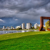 "Description from Wikipedia: Gate to the Northwest Passage is a 1980 sculpture by Alan Chung Hung, located adjacent to the Vancouver Maritime Museum in Vanier Park in the Kitsilano neighbourhood of Vancouver, British Columbia, Canada. The 4.6-metre (15 ft) sculpture of a square, cut and twisted ""like a paper clip"" to form an arch, is composed of weathered Corten steel that rusts to provide a protective layer. The work was installed in 1980 to commemorate the arrival of Captain George Vancouver in Burrard Inlet, following a competition sponsored by Parks Canada one year prior. Gate to the Northwest Passage received an adverse reaction initially, but reception has improved over time. The sculpture has been included in walking tours of the surrounding neighborhoods as a highlight of Vanier Park."