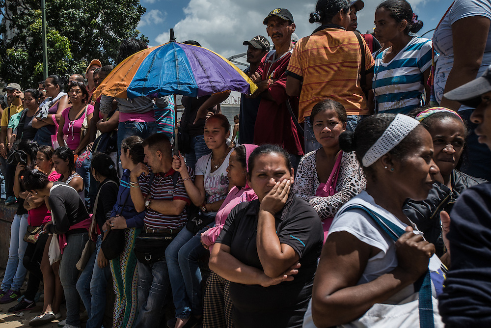 "CARACAS, VENEZUELA - JUNE 11, 2016:  Hundreds of people wait in line to buy food outside of a grocery store in Catia, a slum in western Caracas. The shoppers had arrived as early as 3 am, and waited in line for over eight hours before they were told to go home because there was no more food available for them to buy.  Dozens of people in the line started to protest, exasperated by being told to go home empty handed, after waiting for so long.  When the crowd became unruly, armed ""collectivos"" of government loyalists arrived and threatened them, beating one man. The protesting shoppers refused to stop, shouting ""we are hungry!"" until anti-riot police arrived and calmed everyone down.  PHOTO: Meridith Kohut for The New York Times"