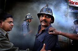 Indian firemen attempt to put out a rapidly spreading fire in a Muslim neighborhood of central Ahmedabad, India, on March 1, 2002.