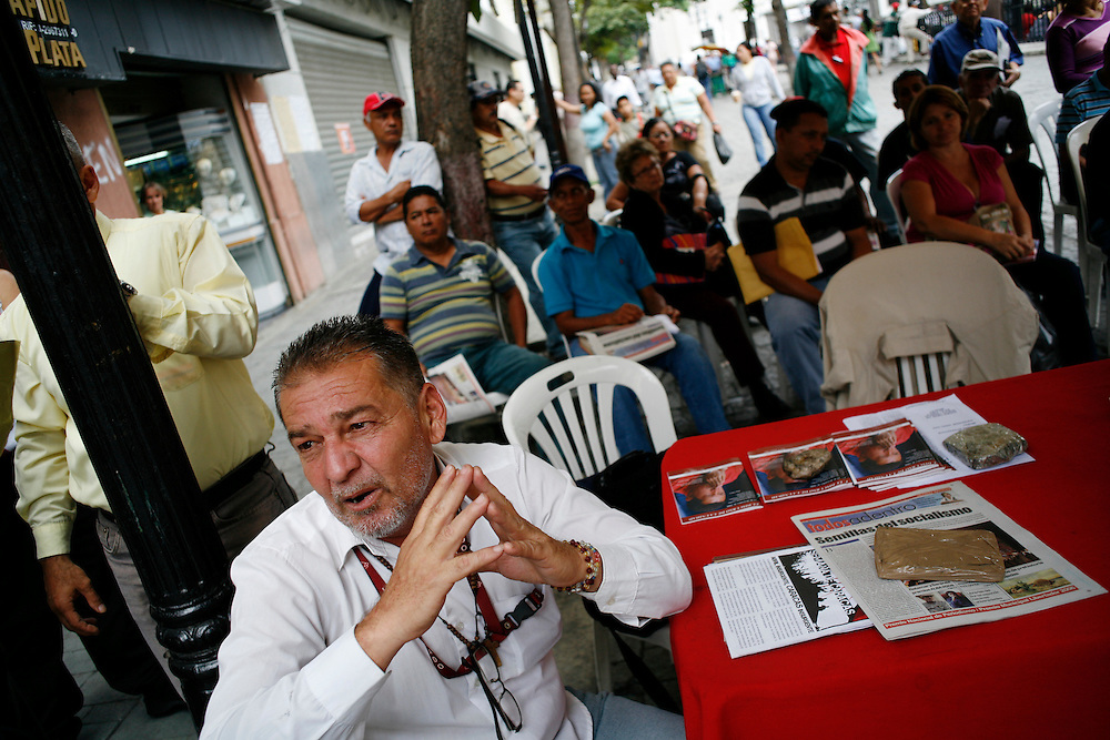 A volunteer organizer manages a tent just outside Plaza Bolivar in downtown Caracas. He helps answers questions from passesrby and mediates discussion among the visitors.
