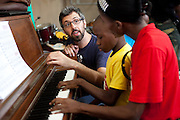 Volunteer music instructor Alex Ballentine, from the US, teaches a piano lesson on the first floor.