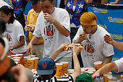 NEW YORK, NY-06 JUL04-- Sonya Thomas, American favourite Joey Chestnut and Titleholder Takeru Kobayashi go for the gold (well, yellow to be precise). (Extra) Liam Maloney/The Gazette