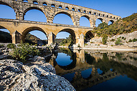 The Pont du Gard was built to allow the aqueduct of Nimes, which is almost 50 km long, to cross the Gard river. The Roman architects and engineers who designed this bridge and aqueduct created a technical as well as an artistic masterpiece. A true masterpiece of ancient architecture, the Pont du Gard aqueduct is one of the most beautiful Roman constructions in Europe and was added to the UNESCO World Heritage Sites list 1985.  The full aqueduct had a gradient of 34 cm/km descending 17 meters in its entire length and delivering 20,000 cubic meters of water daily. Incredibly, it was constructed entirely without the use of mortar.  From the 4th century its maintenance was neglected, and deposits filled up the conduit space. Most of the Pont du Gard remains intact. The aqueduct was restored in the 18th century, by which time it had become a major tourist sight, and was restored again in the 19th century.