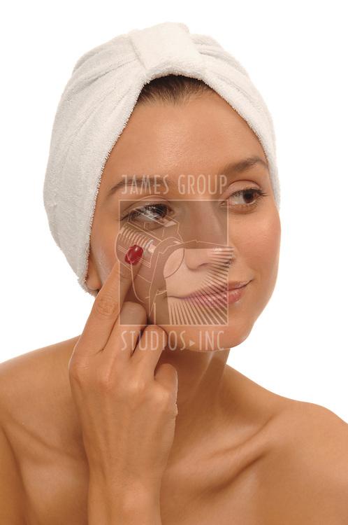 Beautiful young woman wearing spa turban, applying anti-wrinkle cream below the eye