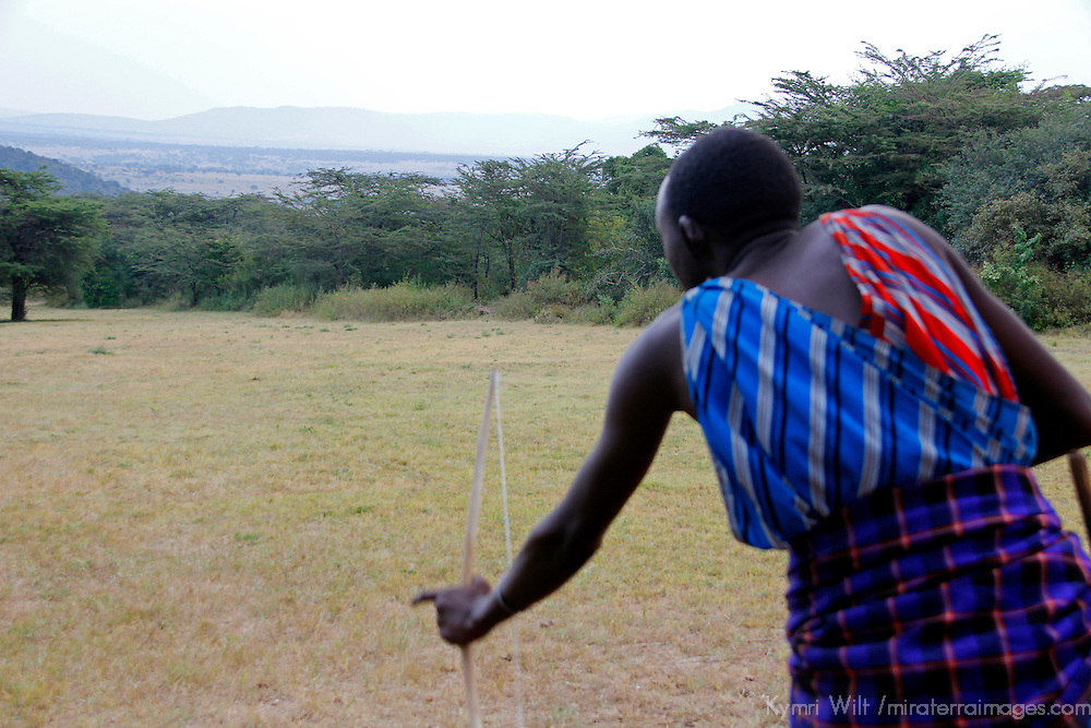 Africa, Kenya, Masai Mara. Maasai Warrior demonstrates archery skills for visitors to Cottar's 1920's safari Camp.