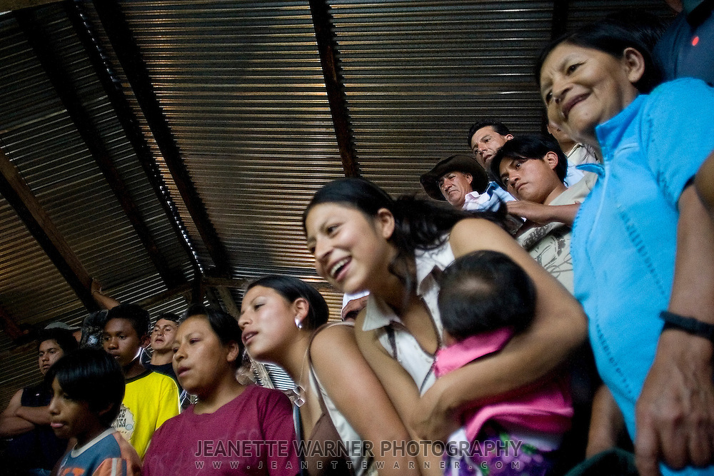 Women watch one of the fights from the stands.  Many wives attend in order to support their husbands, oftentimes bringing their kids along.  While the women say they enjoy watching the cockfights, they also say they enjoy the social time with the other women..