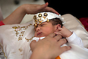 A head band of good luck charms is placed on the head of Tunisian Jewish 8 day -old male baby  Avi Ishai after a circumcision was performed on the  newborn at the home of the Hori family that lives in the Hara Kebira neighborhood  in  Djerba on May 25,2016. (Photo by Heidi Levine).