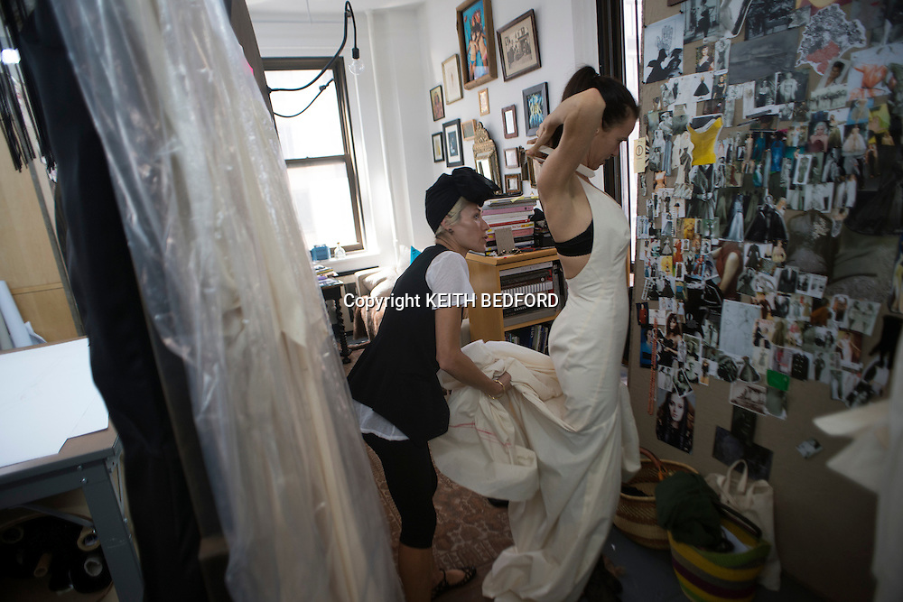 ATTEN FOR MAGAZINE DESK - Fashion designer Norisol Ferrari puts oner of her dresses on her friend Mary Lee( R) as she prepares her collection for New York Fashion Week at her studio in New York, August 29, 2012.  Ferrari will be presenting her collection for the first time on the runway at New York's Fashion Week on September 10, 2013.  Picture taken on August 29, 2012. REUTERS/Keith Bedford  (UNITED STATES),