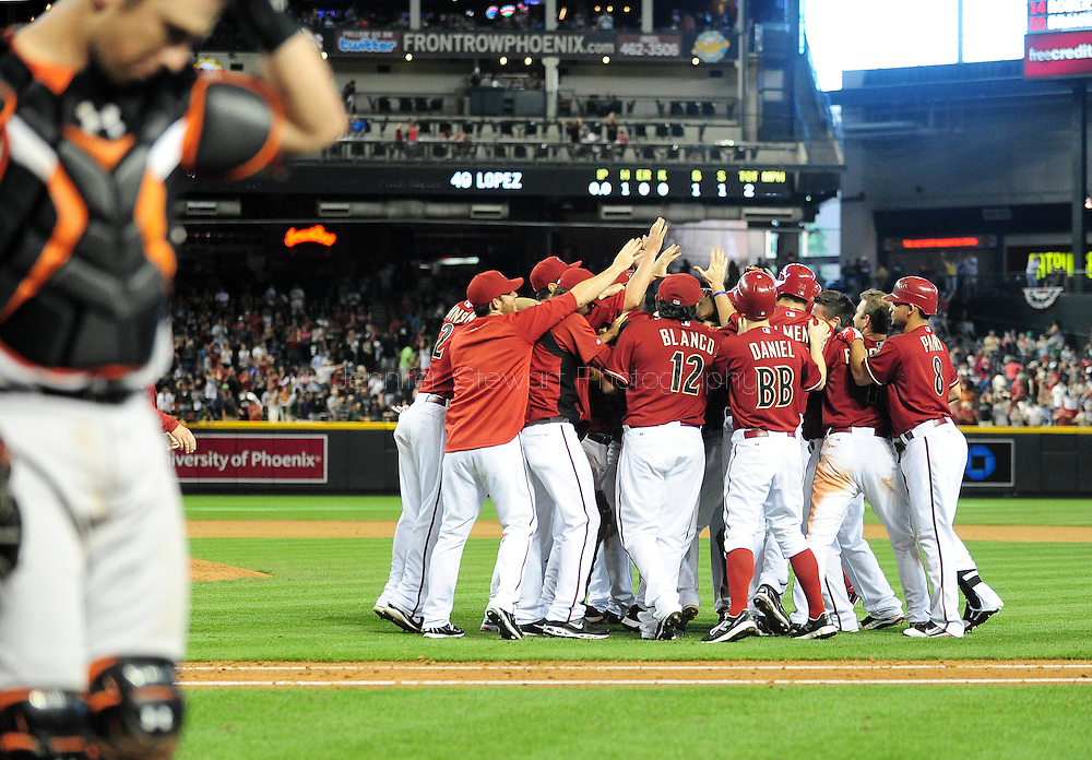 Apr. 17 2011; Phoenix, AZ, USA; Arizona Diamondbacks batter Stephen Drew (6) celebrates with teammates after hitting the game winning single during the twelfth inning as the San Francisco Giants catcher Buster Posey (28) walks to the dugout at Chase Field. The Diamondbacks defeated the Giants in extra innings 6-5. Mandatory Credit: Jennifer Stewart-US PRESSWIRE.