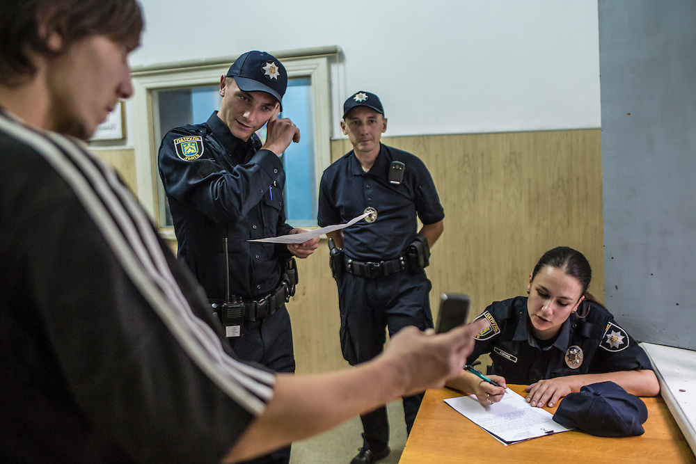 LVIV, UKRAINE - SEPTEMBER 16, 2015: Tetiana Soroka, 25, right, a member of the new Lviv police, fills out paperwork connected with the arrest of Vladimir, 26, left, after he was found intoxicated and sleeping in the city's central square and then swore at police officers in Lviv, Ukraine. In an effort to reform the notoriously corrupt Ukrainian police force, an entirely new force has been established in several cities, including Kiev and Lviv, with a primary focus on patrolling the streets. CREDIT: Brendan Hoffman for The New York Times