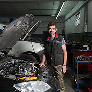 Car mechanic Michalis Paraskevas 28,  member of the TEM network (local alternative currency ) in his workshop in Volos. He is charging the spare parts in euros and his work in TEMs.