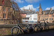 Bikes against a canal wall in Bruges