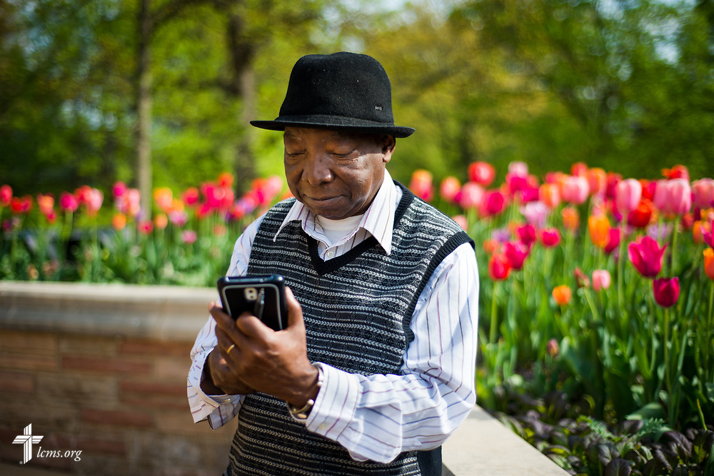 The Rev. Dr. John Loum, director, Ethnic Immigrant Institute of Theology and new career missionary to Africa,  works on his mobile phone outside the Chapel of St. Timothy and St. Titus on Wednesday, April 19, 2017, at Concordia Seminary, St. Louis. LCMS Communications/Erik M. Lunsford