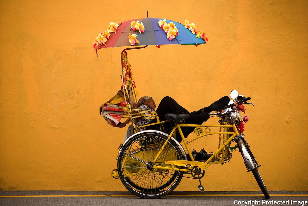 a trishaw driver takes a rest