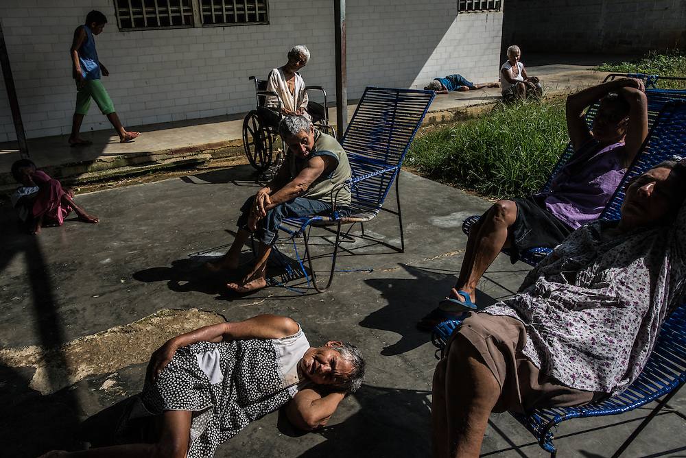 BARQUISIMETO, VENEZUELA - JULY 29, 2016: Patients pass the hours in the patio of the women's ward. The economic crisis that has left Venezuela with little hard currency has also severely affected its public health system, crippling hospitals like El Pampero Psychiatric Hospital by leaving it without the resources it needs to take care of patients living there, the majority of whom have been abandoned by their families and rely completely on the state to meet their basic needs. The hospital has not employed a psychiatrist for over two years. The halls are filled with sounds of patients crying or screaming, and an overpowering stench of urine and feces.  Drugs used to combat bipolar disorder, epilepsy, schizoaffective disorder and chronic anxiety are now in short supply, as are numerous sedatives and tranquilizers needed to care for patients. Members of the nursing staff debate daily which patients are the most unstable, to decide which patients will receive pills and which will go without. When a patient loses control, often the only thing they can do is lock them in an isolation cell to prevent them from hurting themselves, other patients and members of the staff. The hospital does not even have basic hygiene or cleaning supplies.  There is no soap, no shampoo, no tooth paste, no toilet paper.  Patients relieve themselves in the common areas and patio area, and clean themselves only with water. Nearly every patient is infected with scabies because they do not have the resources to bathe properly or to have their threadbare, misfitted clothes washed as often as needed. To make matters worse, the hospital only has running water a few hours a day.  PHOTO: Meridith Kohut