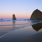 The earth's shadow is visible just over the horizon in this sunrise image of Haystack Rock, a prominent sea stack in Cannon Beach on the Oregon Coast. The reddish band above the earth's shadow is known as the Belt of Venus. Haystack Rock, at 235-feet, ranks as the world's third-tallest sea stack.