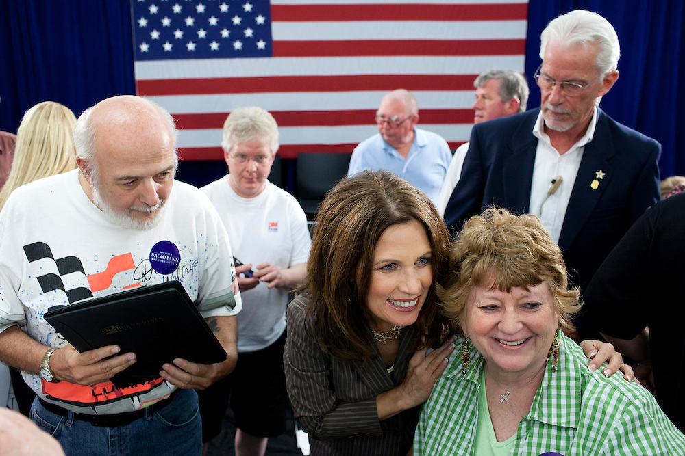 Republican presidential hopeful Michele Bachmann, center, poses for pictures at a campaign stop on Saturday, July 23, 2011 in Marshalltown, IA.