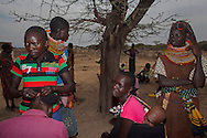 Haidresser Jeni Echua 15, brades the hair of a mother, first left,  as baby Robert Tikai, five months, is nestled in a sling on her mothers back, Mary Albunu, second right, during a gathering of the mother to mother group at Manyatta Zebra, Isiolo county, Kenya Thursday, Feb. 13, 2014. Mother-to-mother support group in the village of Manyatta Zebra, teach women about hygiene and sanitation, nutrition, how to breastfeed, the importance of going to antenatal check-ups and delivering in hospital. Just as important it has generated a sense of community  and solidarity in the town's child bearing women and created an exchange of information  and knowledge between mothers.