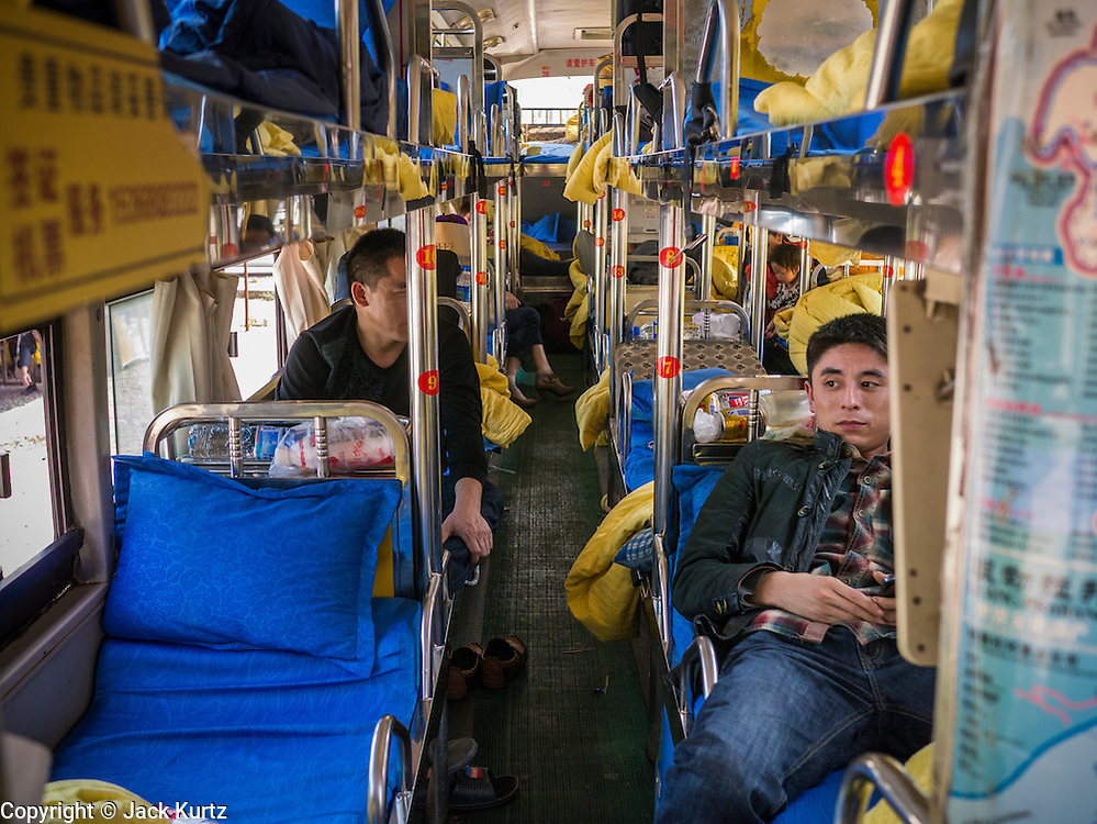 13 MARCH 2013 - ALONG HIGHWAY 13, LAOS: A Chinese tourist relaxes on a sleeper bus to Luang Prabang on Highway 13 in the Boten Special Economic Zone. The SEZ is in Laos immediately south of the Lao Chinese border. It has turned into a Chinese enclave but many of the businesses struggle because their goods are too expensive for local Lao to purchase. Some of the hotels and casinos in the area have been forced to close by the Chinese government after reports of rigged games. The paving of Highway 13 from Vientiane to near the Chinese border has changed the way of life in rural Laos. Villagers near Luang Prabang used to have to take unreliable boats that took three hours round trip to get from the homes to the tourist center of Luang Prabang, now they take a 40 minute round trip bus ride. North of Luang Prabang, paving the highway has been an opportunity for China to use Laos as a transshipping point. Chinese merchandise now goes through Laos to Thailand where it's put on Thai trains and taken to the deep water port east of Bangkok. The Chinese have also expanded their economic empire into Laos. Chinese hotels and businesses are common in northern Laos and in some cities, like Oudomxay, are now up to 40% percent. As the roads are paved, more people move away from their traditional homes in the mountains of Laos and crowd the side of the road living off tourists' and truck drivers.    PHOTO BY JACK KURTZ