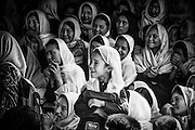 Girls in their school uniform show smile as they see theatrical performance by children.