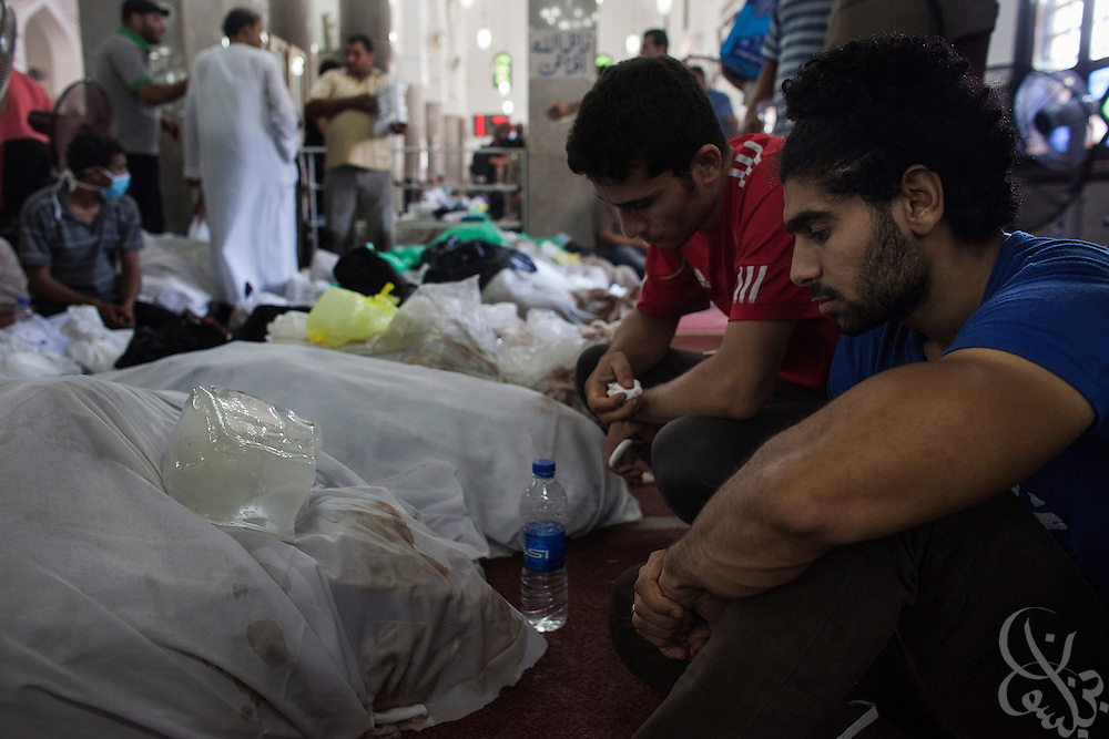 Hussam Nabil Abdullah (l) sits quietly in front of the wrapped body of his father inside the Iman mosque August 15, 2014  in the Nasr City district of Cairo, Egypt.  A day after violent raids by security forces on sit-in protest camps of the supporters of deposed Egyptian President Mohamed Morsi, the country is trying to come to terms with the news that at least 600 people were killed and thousands more injured.