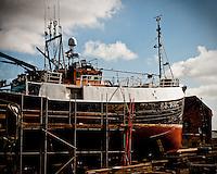 Grimsby Docks, a small trawler sits on the slipway undergoing maintenance.