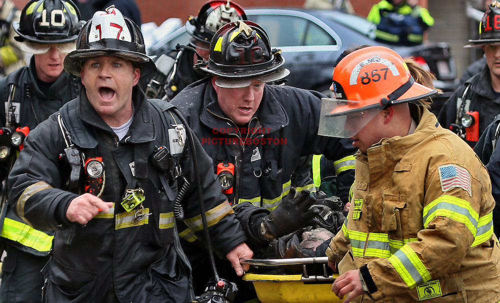 03/26/14-Boston,MA. Boston firefighters carry firefighter Michael Kennedy from 298 Beacon St. after a large wind-whipped fire claimed the Back Bay building, killing 2 firefighters and injuring several today, March 26, 2014. Photo: Mark Garfinkel/Boston Herald