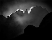 The three summits of Sterkhorn 2973m, also known as Mount Memory or Mount Mandela, seen backlit at sunrise from Keith Bush Camp as morning mist dissipates in the uMhlwazini Valley.  Ukhahlamba-Drakensberg Park, South Africa.  Nikon F90, 50-135/3.5. Fuji RD. October 1995