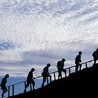 Ecuador, Galapagos Islands, Silhouette of tour group climbing stairs to summit of Bartolomé Island