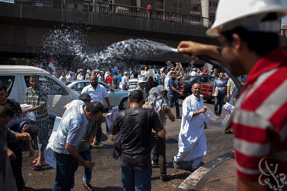 Supporters of deposed Egyptian president Mohamed Morsi are sprayed with cool water as they march to continuing large scale demonstrations and a sit-in around the Rabaah al-Adawia mosque and square in the Nasr City district of Cairo Friday July 26, 2013.  The supporters are demanding the reinstatement of the deposed President and are opposed to the Egyptian military, which they say has undertaken an undemocratic coup.