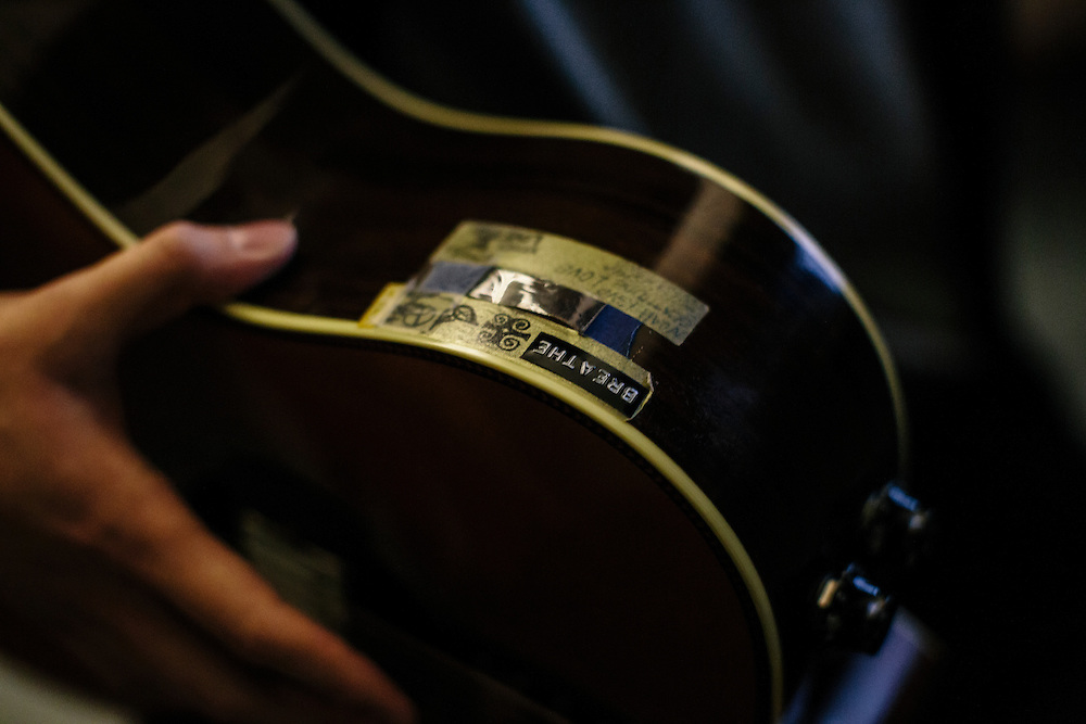"""Roy Kim holds his Martin guitar, a John Mayer signature edition, one that he says he used when he won Superstar K. On the guitar he has various words, such as """"love from fans"""" and """"humble,"""" reminders for while he's on stage to stay in the moment. Kim became a South Korean pop star after winning Superstar K4, his country's version of American Idol."""