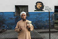 """Dawud in a suburb of Havana in front of a murale representing Che Guevara. His gesture with the index finger up means """"Allah is one""""."""